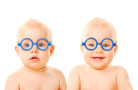 Two twins babies boys wearing glasses.